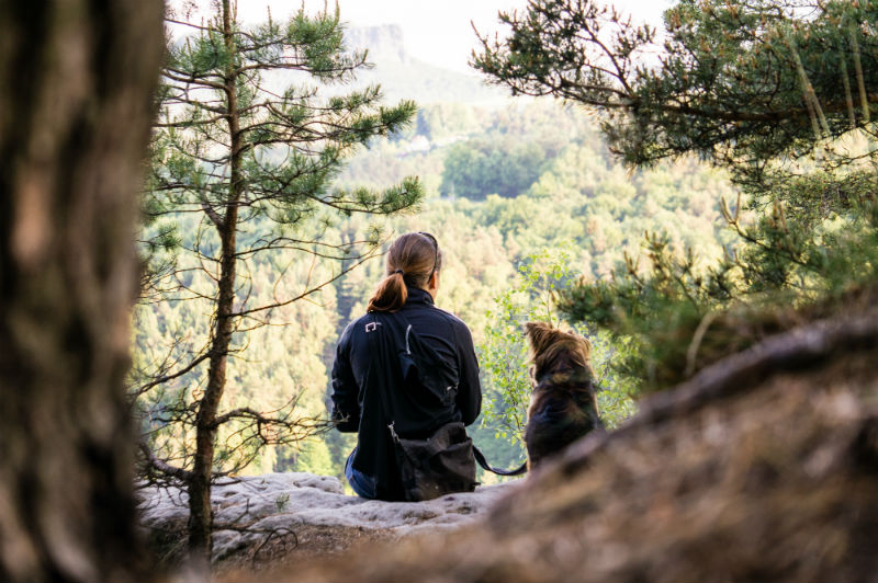 A woman and a dog sitting on top of a cliff